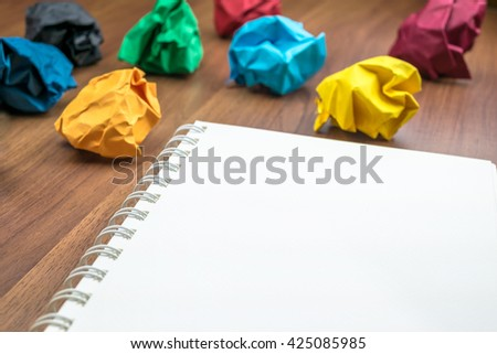 open blank ring binder white book  with group of colorful crumpled paper ball on dark brown table top, Business Brainstorming concept,mock up for adding your text - stock photo
