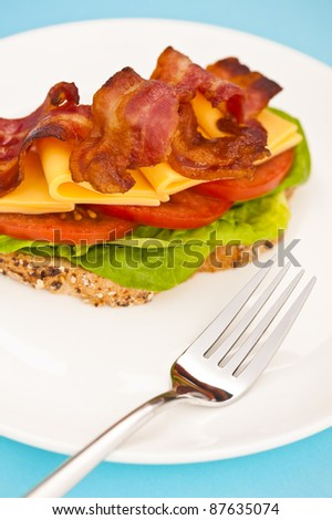 Open blt sandwich on a white plate with blue background and fork - stock photo