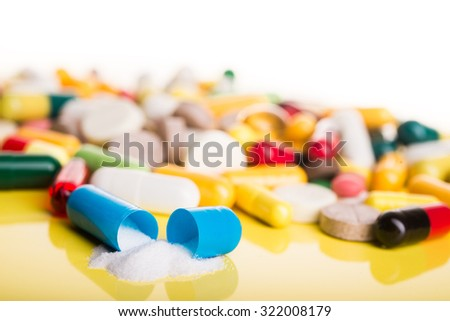 Open blue capsule with white drug on white background