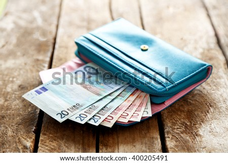 Open blue purse with euro banknotes on wooden table - stock photo