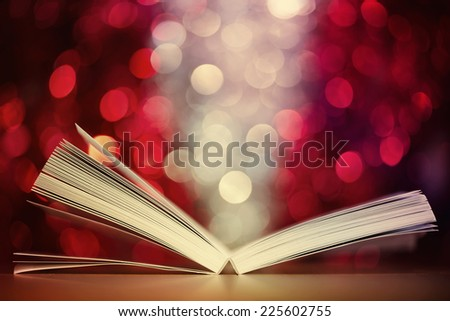 Open book against red and white defocused lights background