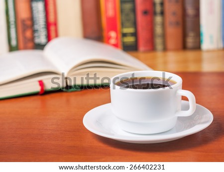 Open book and a cup of coffee in the library