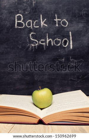 open book and a green apple in front of blackboard - stock photo
