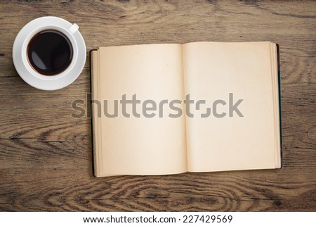 open book and coffee top view on table - stock photo