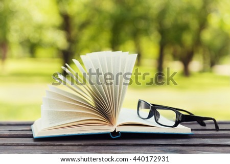 Open book and eyeglasses on a bench in park in a sunny day, reading in the summer, education, textbook, back to school concept - stock photo