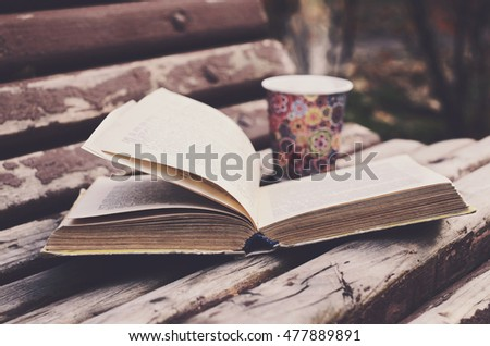 Open book and hot drink on wooden bench in autumn garden