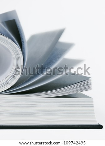 Open book and pages in motion - stock photo