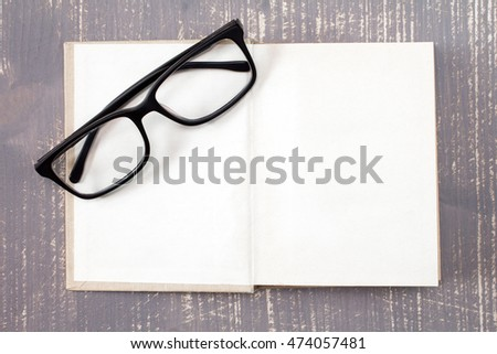 Open book and reading glasses on the wooden background.Top view.