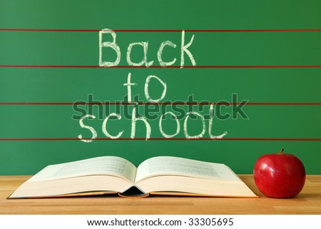 Open book and red apple on desk with back to school written on the chalkboard - stock photo