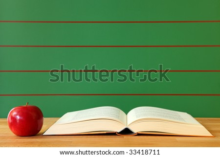 Open book and red apple on desk with empty chalkboard - stock photo