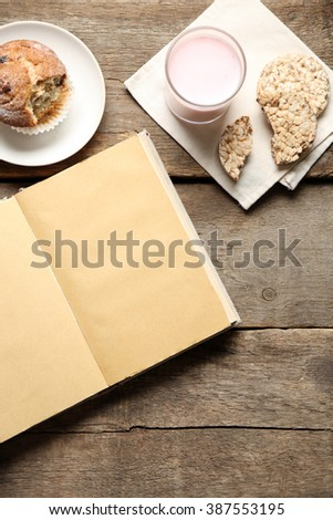 Open book and snack on wooden table background