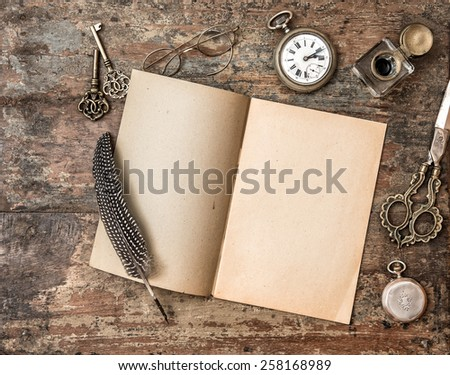 Open book and vintage writing on wooden table. Feather pen, inkwell, keys on textured background - stock photo