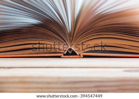 Open book background on wooden table, selective focus - stock photo