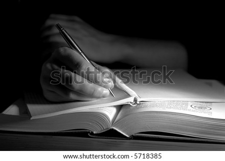 Open book in a dark room, with uman hand taking notes