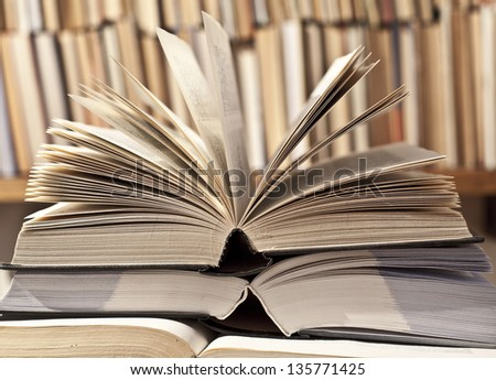 open book in a library on bookshelf background - stock photo