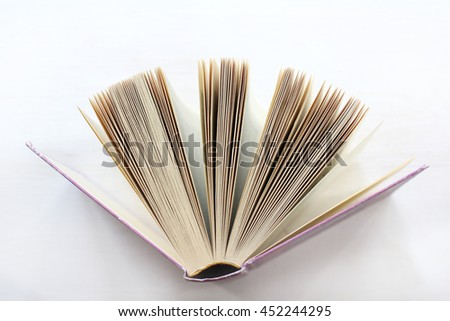 open book in a pink hardcover and many pages, stands on a light background / knowledge source