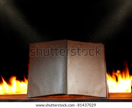 open book in ambient light with fire on background