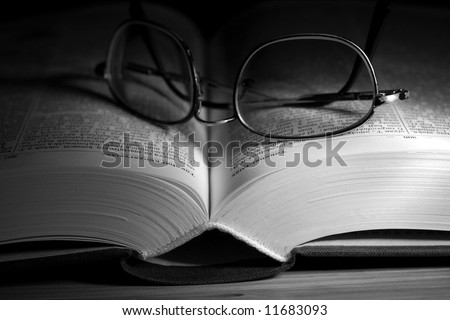 Open book in black and white with glasses on it