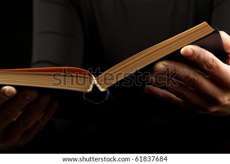 Open book in hands on black background