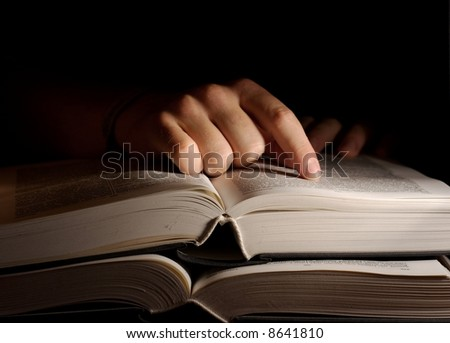 Open book in the dark with a hand - stock photo