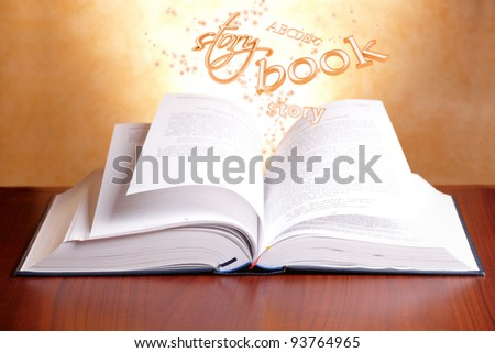 Open book laying on a table with flying words - stock photo