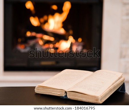 open book lying near the fireplace - stock photo