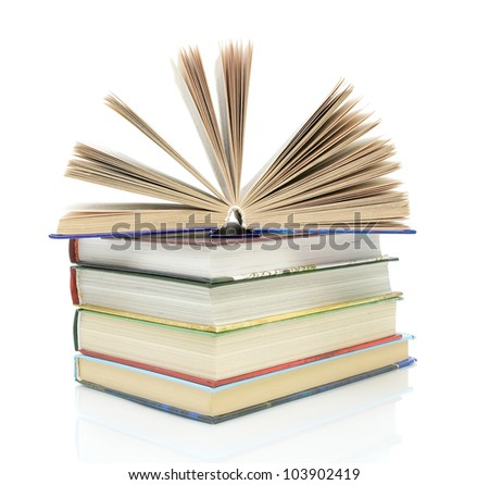 open book on a pile of books on a white background with reflection closeup - stock photo