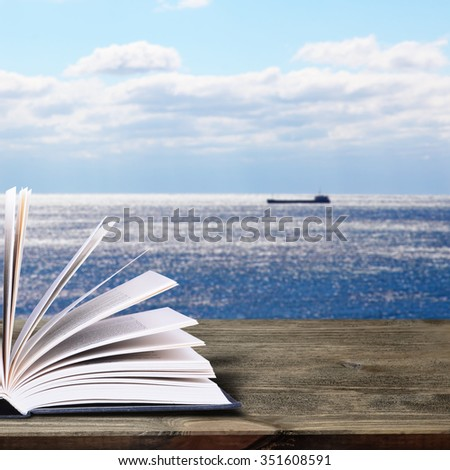 Open book on a rustic wooden table. In the background, a lone ship floats in the sea - stock photo