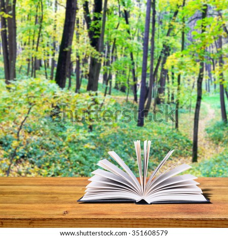 Open book on a rustic wooden table. In the background autumn trees in the park