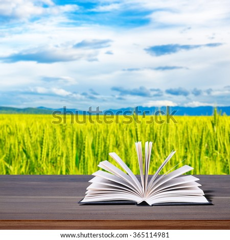 Open book on a rustic wooden table. In the background, the harvest in the wheat field - stock photo