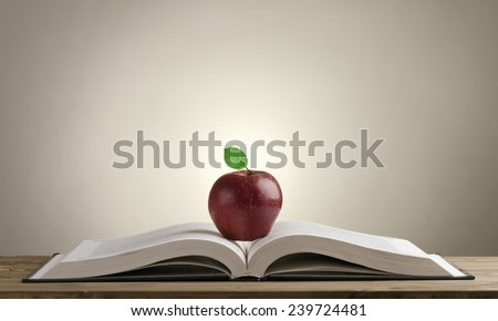 open book on a wooden Desk with a red Apple and green leaves on a grey-lit background.