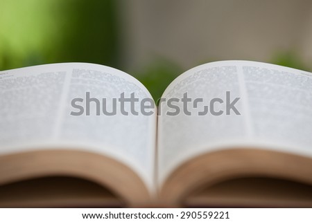 open book on a wooden table in nature, green blurry background - stock photo