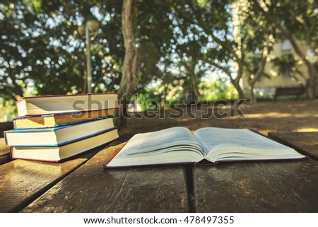 Open book on a wooden table with pile of books on the background.