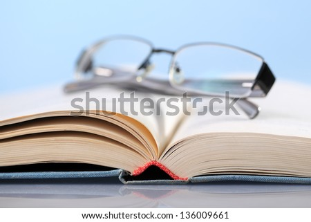 Open book on blue with eyeglasses - stock photo