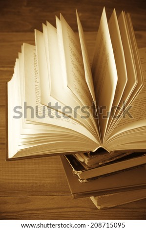 Open book on books stack close-up. Shallow DOF. - stock photo