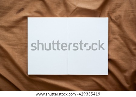 Open book on brown background - stock photo