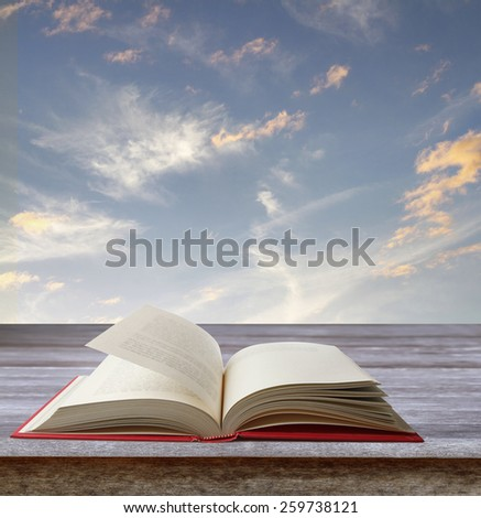 Open book on deck in front of sky - stock photo