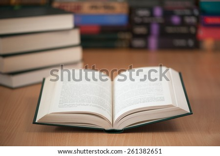open book on library desk with books stacked in the background