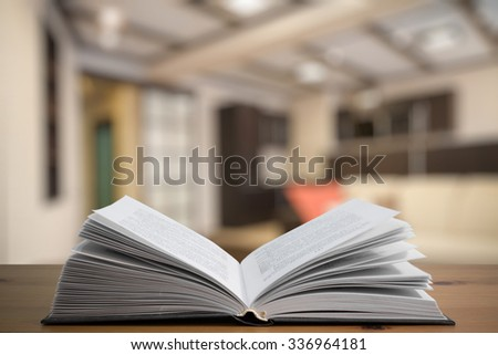 open book on old vintage wooden table in the living room - stock photo