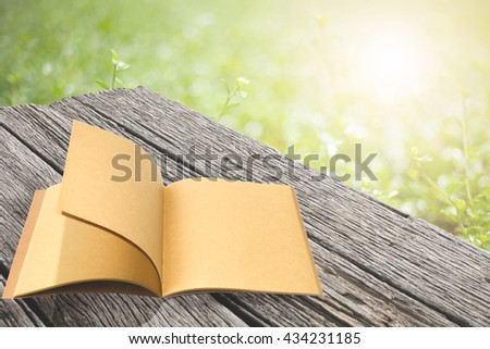 Open book on old wooden planks with abstract blur background is summer scene. - stock photo