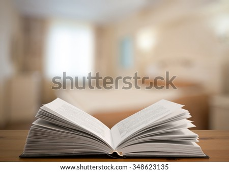 open book on old wooden table in the bedroom - stock photo