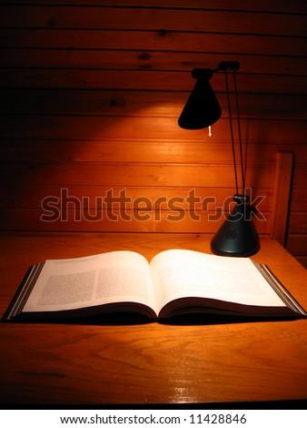 Open book on table alight whit desk lamp - stock photo