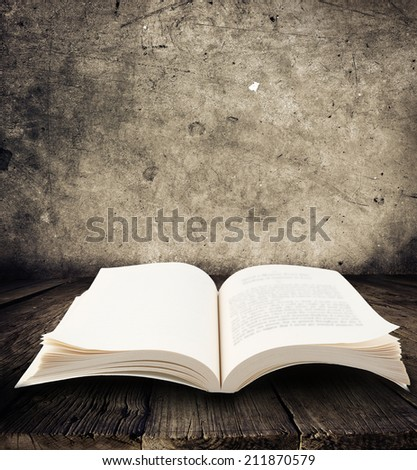 Open book on table in front of blank wall - stock photo