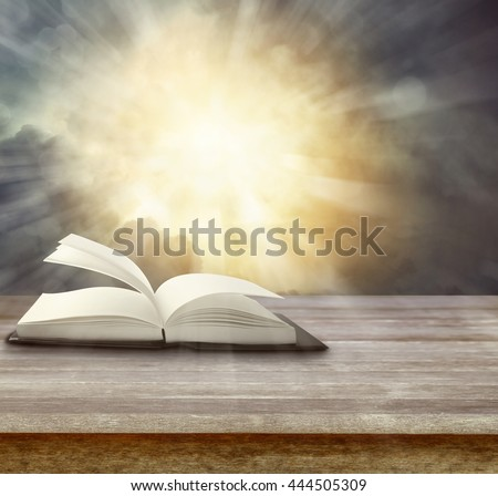 Open book on table in front of bright sky - stock photo