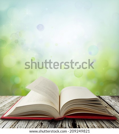 Open book on table in front of green blue  background