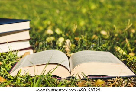 Open book on the grass with pile of closed books on grass background.