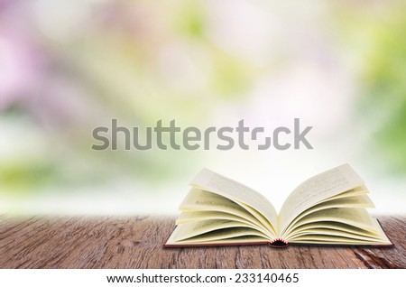 Open book on the wooden table, over abstract light background. - stock photo
