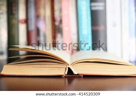 Open book on the wooden table with  books in the background