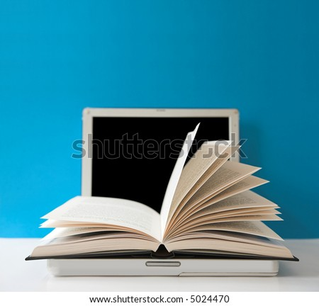 Open book on top of a laptop computer - focus on the tips of the page leaves. - stock photo