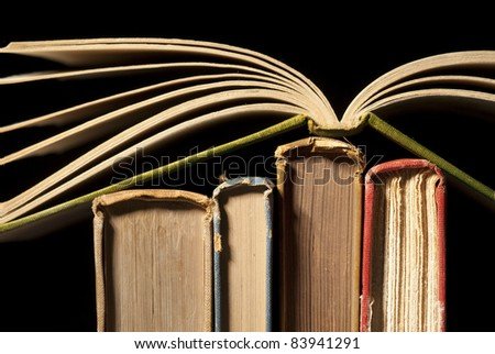 Open book on top of old worn spines on black - stock photo